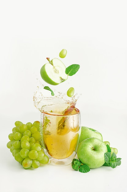 Jabłko, Winogrono I Mięta Przelatują Nad Szklanką Rozpryskującego Się Soku. Koncepcja żywności Biologicznej. Premium Zdjęcia