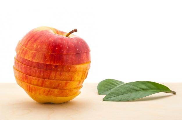 Jabłko zachowało swój kształt, ale pokrojono w plasterki i dwa liście na drewnianym stole. Premium Zdjęcia