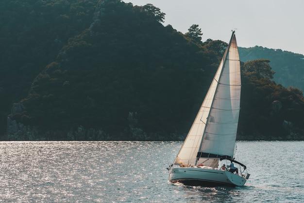 Jacht żaglowy z białymi żaglami na falistej zatoce morskiej w górach. Premium Zdjęcia