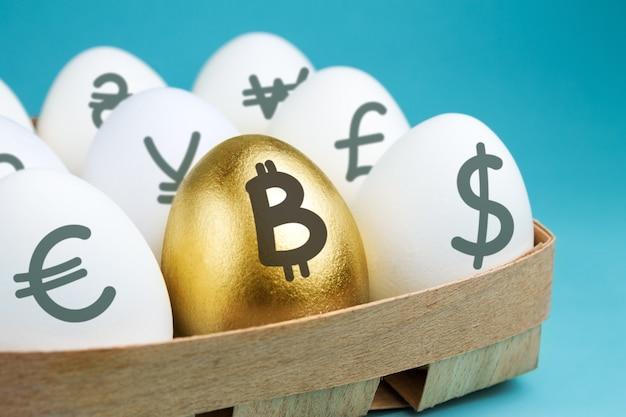Jajka Ze Znakami Waluty W Drewnianym Opakowaniu I Złote Jajko Ze Znakiem Bitcoin Premium Zdjęcia