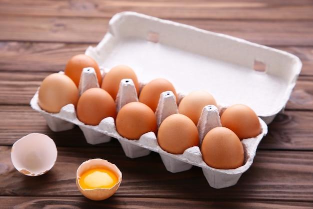 Jajko Kurze Jest W Połowie Połamane Wśród Innych Jaj. Kurczaków Jajka W Zbiornikach Na Brown Drewnianym Tle Premium Zdjęcia