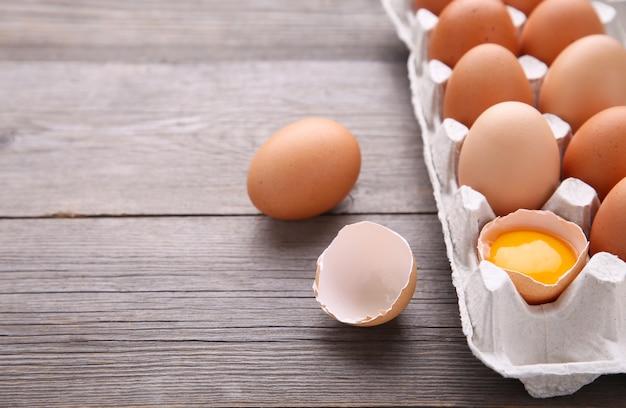 Jajko Kurze Jest W Połowie Połamane Wśród Innych Jaj. Kurczaków Jajka W Zbiornikach Na Szarym Drewnianym Tle Premium Zdjęcia