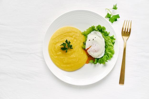 Jajko w koszulce i polenta z sałatą Premium Zdjęcia