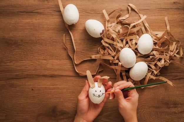Jajko W Ręku Jak Twarz Królika I Inne Białe Jajko Na Drewnianym Stole Premium Zdjęcia