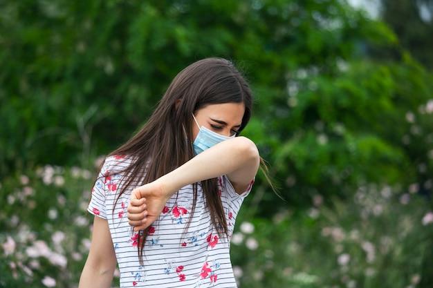 Jak Prawidłowo Kichać. Kobieta Z Maską Ochronną Kicha Na łokciu. Pojęcie Nie Rozprzestrzeniania Się Wirusa. Premium Zdjęcia