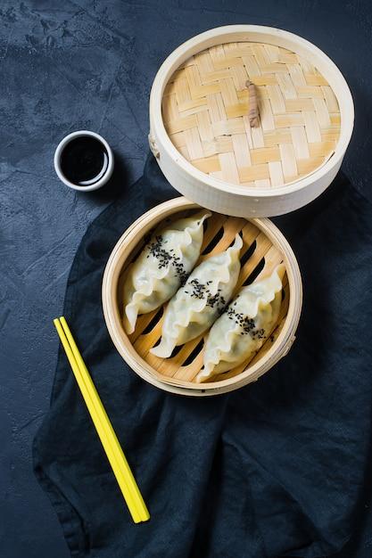 Japoński Gyoza W Tradycyjnym Parowcu, żółte Pałeczki Premium Zdjęcia