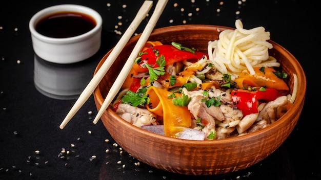 Japoński lub chiński makaron udon z kurczakiem i warzywami Premium Zdjęcia