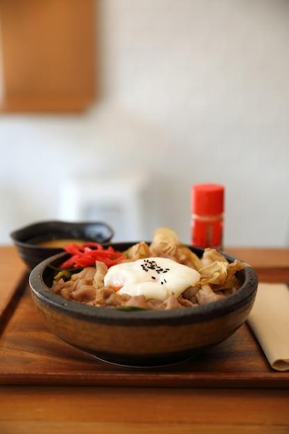 Japońskie jedzenie gyudon japońska wołowina na miskę ryżową zwieńczoną jajkiem na drewnianym stole Premium Zdjęcia