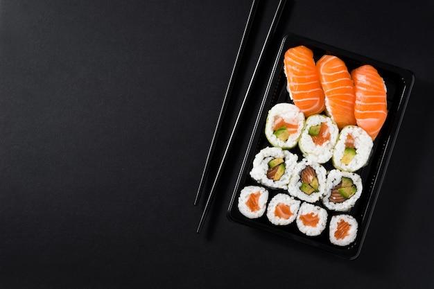 Japońskie Jedzenie: Maki I Nigiri Suszi Ustawiający Na Czarnej Tło Odgórnego Widoku Kopii Przestrzeni Premium Zdjęcia