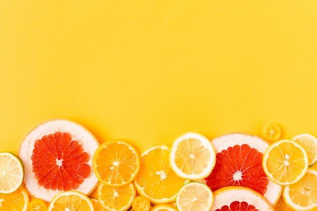 Jaskrawe cytrus owoc na żółtym tle, lata mieszkania nieatutowy pojęcie. Premium Zdjęcia