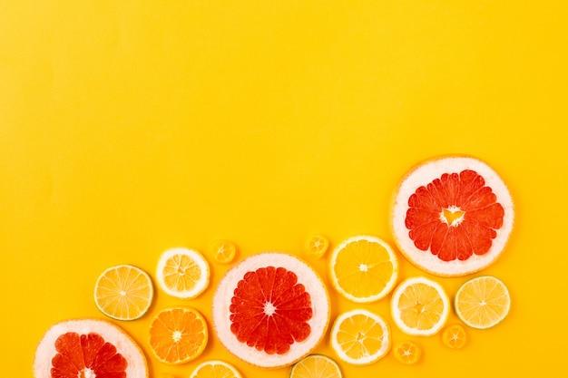 Jaskrawe stubarwne cytrus owoc na żółtym tle, lata mieszkania nieatutowy pojęcie. Premium Zdjęcia