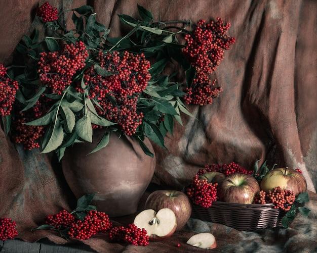 Jaskrawy Czerwony Elderberry W Starym Glinianym Garnku I Jabłkach Na Stole Z Starym Tekstylnym Tłem. Martwa Natura W Stylu Vintage Premium Zdjęcia