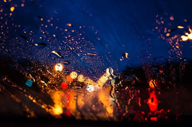Jasne światła nocnego miasta przez szybę w kroplach deszczu. Premium Zdjęcia