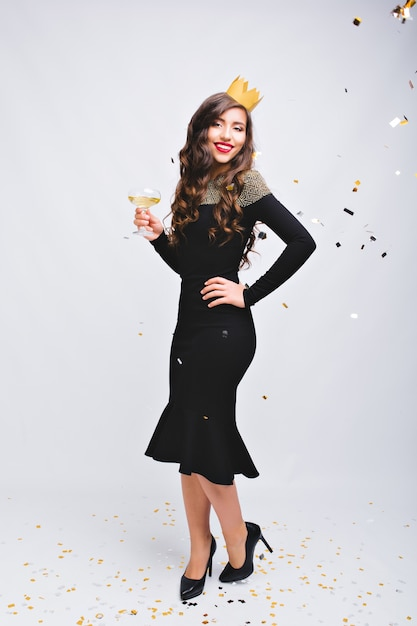 Jasny Karnawał, Przyjęcie Noworoczne Atrakcyjnej Radosnej Kobiety W Luksusowej Czarnej Sukience Na Wysokich Obcasach Na Białej Przestrzeni Darmowe Zdjęcia