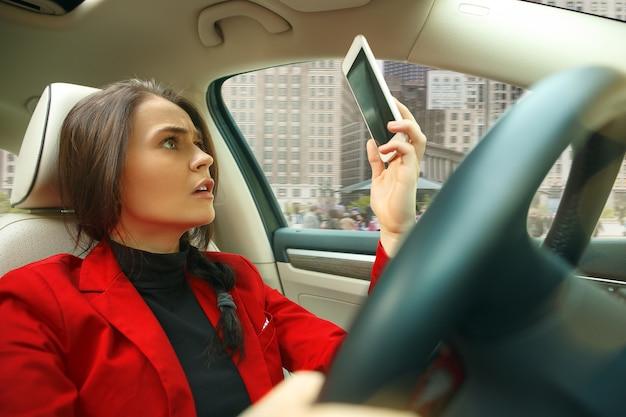 Jazda Po Mieście. Młoda Atrakcyjna Kobieta Podczas Prowadzenia Samochodu Darmowe Zdjęcia