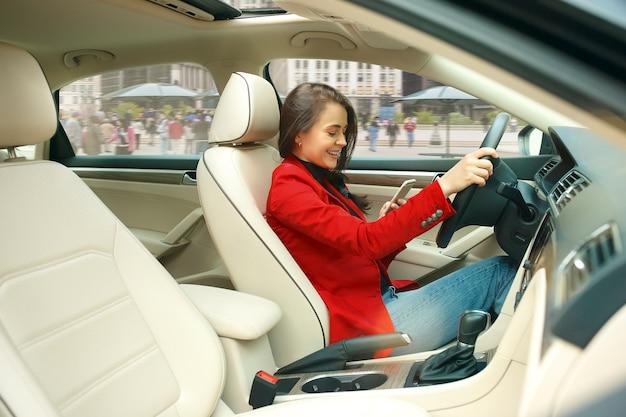 Jazda Po Mieście. Młoda Atrakcyjna Kobieta Podczas Prowadzenia Samochodu. Darmowe Zdjęcia
