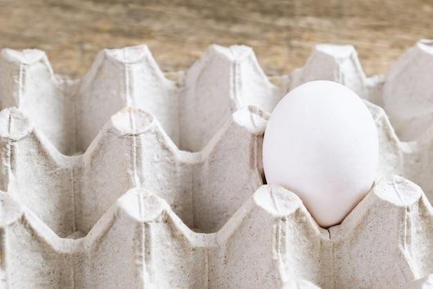 Jeden Biały Jajko W Paczce Na Drewnianym Tle. Darmowe Zdjęcia