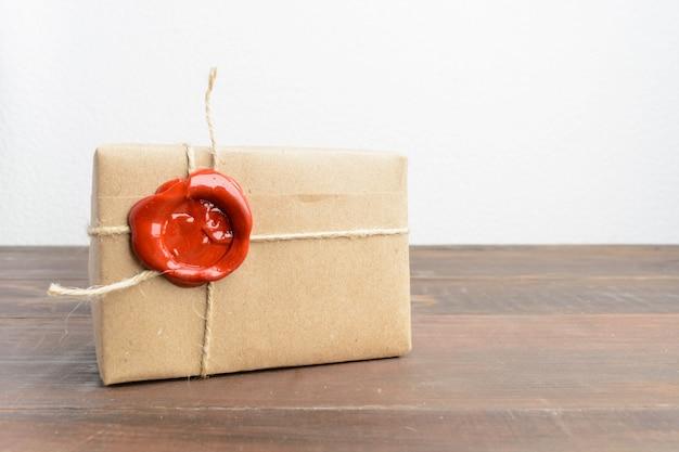 Jeden Obecny W Papierze Rzemieślniczym Z Czerwonym Woskiem Uszczelniającym Nad Drewnianym Stołem Premium Zdjęcia