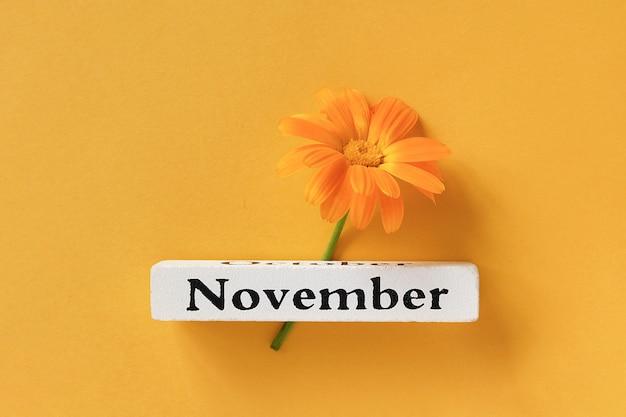 Jeden pomarańczowy kwiat nagietka i kalendarz jesień miesiąc listopad na żółtym tle. Premium Zdjęcia