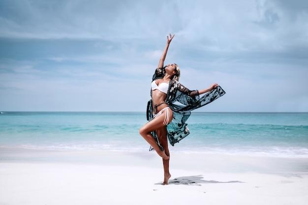 Jeden śliczna piękna blondynka w ubierającej czarnej przejrzystej przylądku i białym kostiumu kąpielowym Premium Zdjęcia