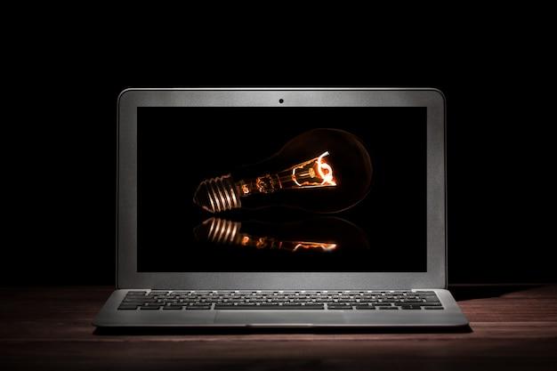 Jeden srebrny nowoczesny laptop ze świecącą żarówką na drewnianym stole w ciemnym pokoju na czarnej powierzchni. Premium Zdjęcia