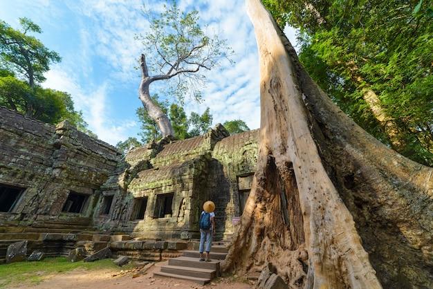 Jeden turysta odwiedzający angkor ruiny wśród dżungli, angkor wat świątynny kompleks, podróży miejsce przeznaczenia kambodża. kobieta z tradycyjnym kapeluszem, tylni widok. Premium Zdjęcia