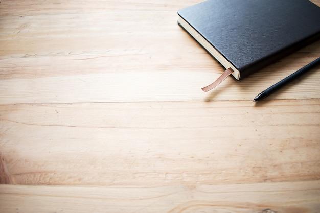 Jedna brązowa książka i długopis umieszczony na starym drewnianym. Premium Zdjęcia