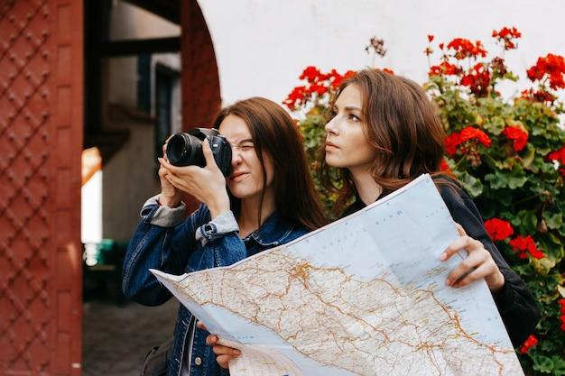 Jedna dziewczyna robi zdjęcie, podczas gdy inna patrzy na mapę turystyczną Darmowe Zdjęcia