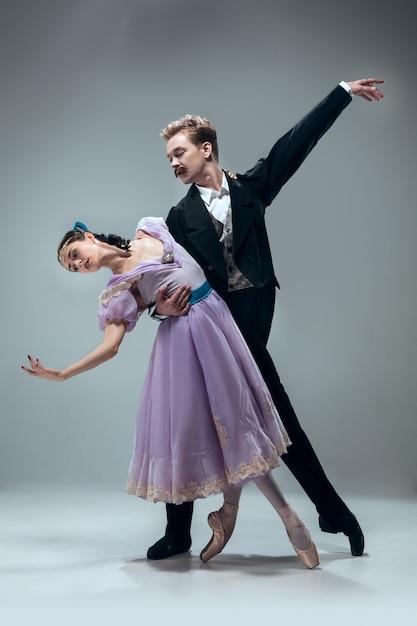 Jedna Jednostka. Piękne Współczesne Tancerzy Balowych Na Białym Tle Na Szarej ścianie. Zmysłowi Profesjonalni Artyści Tańczący Walza, Tango, Slowfox I Quickstep. Elastyczny I Nieważki. Darmowe Zdjęcia