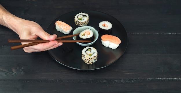 Jedną Ręką Maczanie Bułki Sushi W Sosie Premium Zdjęcia