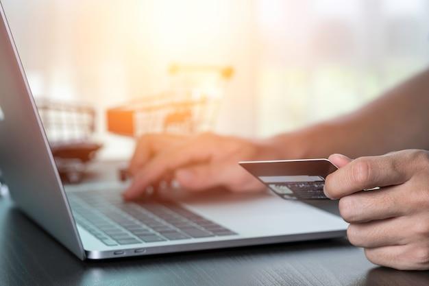 Jedna Ręka Trzyma Kartę Kredytową, A Druga Ręka Wkłada Zamówienie Na Komputer Laptop Z Tłem Karty. Zakupy Online I Praca Z Domu Koncepcji. Premium Zdjęcia