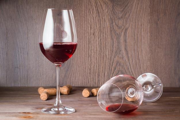Jedna Szklanka Z Resztkami Czerwonego Wina Leży, Druga Stoi Wypełniona Czerwonym Winem I Korkiem Na Drewnianym Stole Premium Zdjęcia