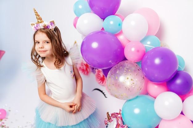 Jednorożec Dziewczyna Pozuje W Pobliżu Balonów Na Przyjęcie Urodzinowe Premium Zdjęcia