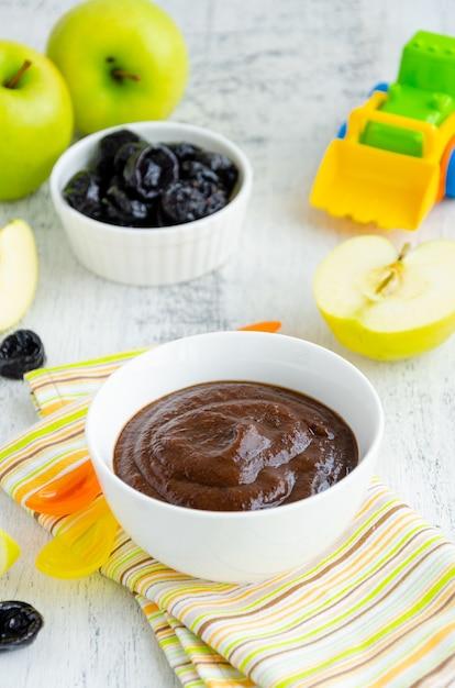 Jedzenie Dla Dzieci. Domowe Puree Z Zielonych Jabłek I Suszonych śliwek Premium Zdjęcia
