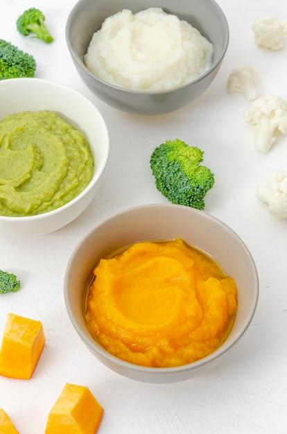 Jedzenie Dla Dzieci. Odmiana Trzech Przecierów Warzywnych W Miseczkach. Puree Z Dyni, Przecier Z Kalafiora I Puree Z Brokułów Premium Zdjęcia