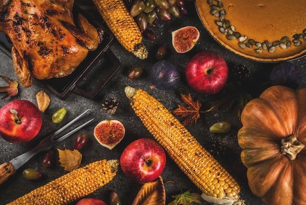 Jedzenie Na święto Dziękczynienia. Pieczony Kurczak Lub Indyk Z Jesiennymi Warzywami I Owocami: Kukurydza, Dynia, Ciasto Z Dyni, Figi, Jabłka, Na Ciemnoszarym Tle, Widok Z Góry Premium Zdjęcia