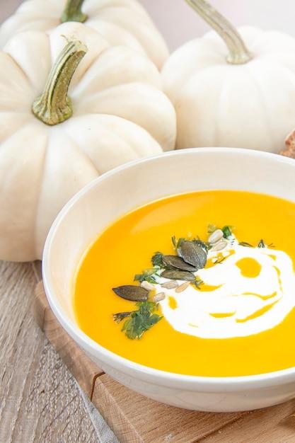 Jedzenie sezonowe. zupy dyniowe. zupa ozdobiona sosem śmietanowym i pestkami dyni. Premium Zdjęcia