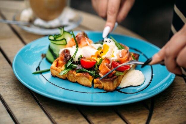 Jedzenie Tostów Waflowych Z Jajkiem W Koszulce I łososiem Na Drewnianym Stole Premium Zdjęcia