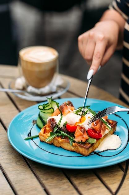 Jedzenie Tostów Waflowych Z Jajkiem W Koszulce I łososiem Z Kawą Premium Zdjęcia