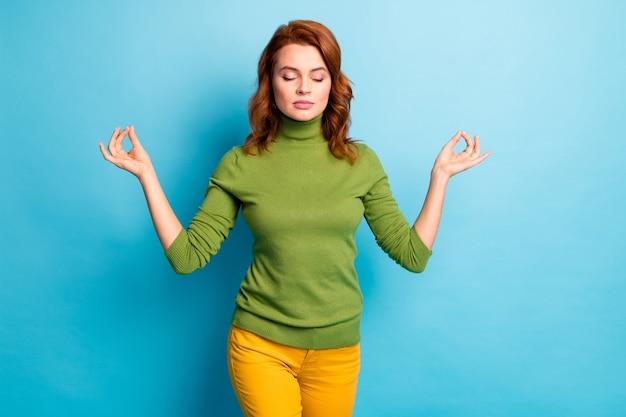 Jej Portret Jest ładną Atrakcyjną Pogodną Spokojną Falistą Dziewczyną Pokazującą Gest Om Medytujący Na Białym Tle Nad Jasnym, żywym Połyskiem żywy Niebieski Turkusowy Turkusowy Kolor ściany Premium Zdjęcia