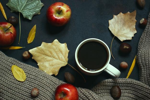 Jesień, jesienne liście, gorąca parująca filiżanka kawy i ciepły szalik lub kardigan. sezonowa, poranna kawa, niedzielny relaks i martwa natura. Darmowe Zdjęcia