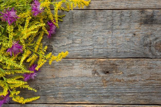 Jesień Kwiaty Na Drewnianym Nieociosanym Tle. Skopiuj Miejsce Premium Zdjęcia