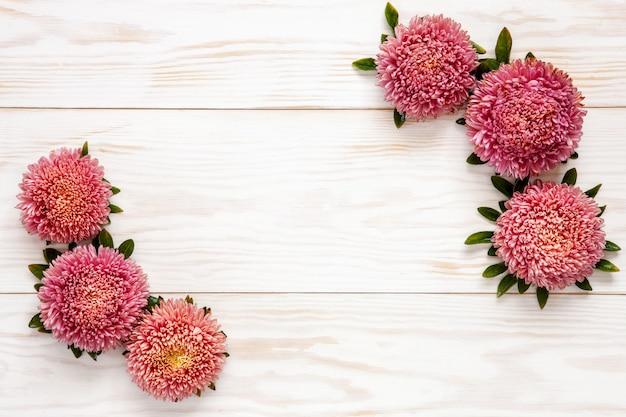 Jesieni Kwiecisty Tło - Różowi Astery Na Białym Drewnianym Stole. Premium Zdjęcia