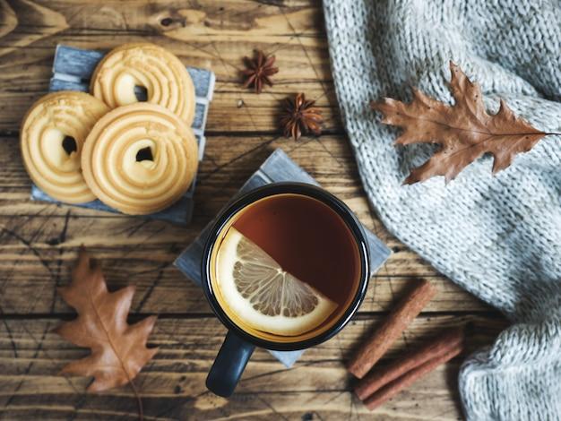 Jesieni wciąż życie z filiżanką herbata, ciastka, pulower i liście na drewnianym stole. Premium Zdjęcia