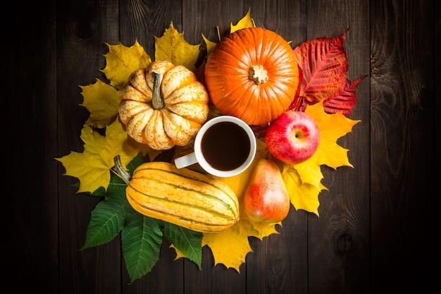 Jesienna dekoracja tło z dyni, szpiku, jabłka, gruszki, filiżanki kawy i kolorowych liści na ciemnym tle drewnianych. Premium Zdjęcia