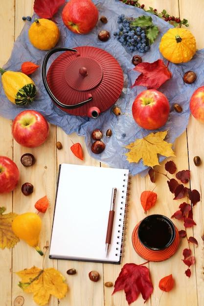 Jesienna herbata. notatnik z czerwonym czajnikiem, filiżanka z herbatą, liście klonu, kasztany, jabłka, dynia. Premium Zdjęcia