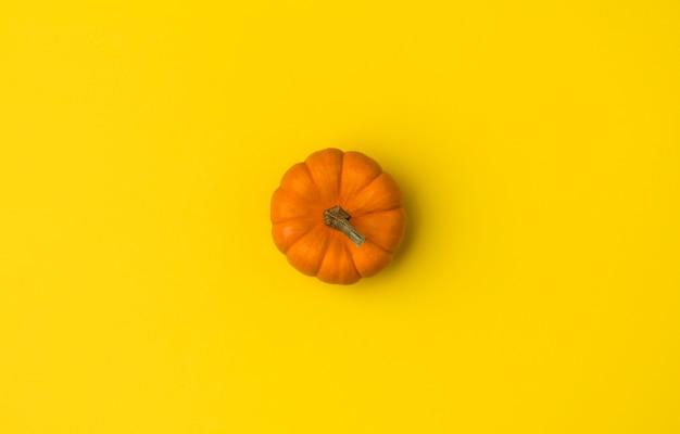 Jesienna płaska świecka kompozycja. dynia na żółtym stole. Premium Zdjęcia