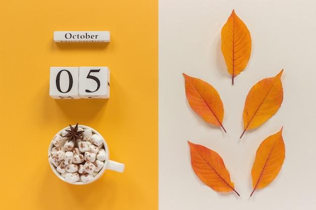 Jesienny kalendarz, 5 października, filiżanka kakao z piankami i żółte jesienne liście Premium Zdjęcia