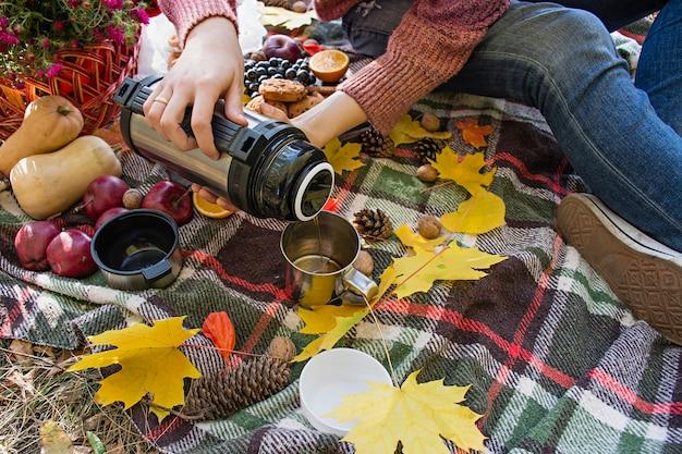 Jesienny piknik w parku. dziewczyna nalewa herbatę z termosu do filiżanki. Premium Zdjęcia