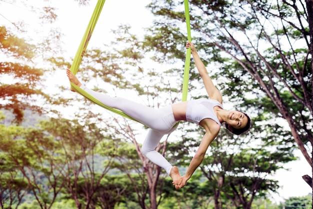 Joga antygrawitacyjna lub powietrzna joga na wolnym powietrzu z publicznym parkiem; mucha akrobatyczna; pilates i d Premium Zdjęcia